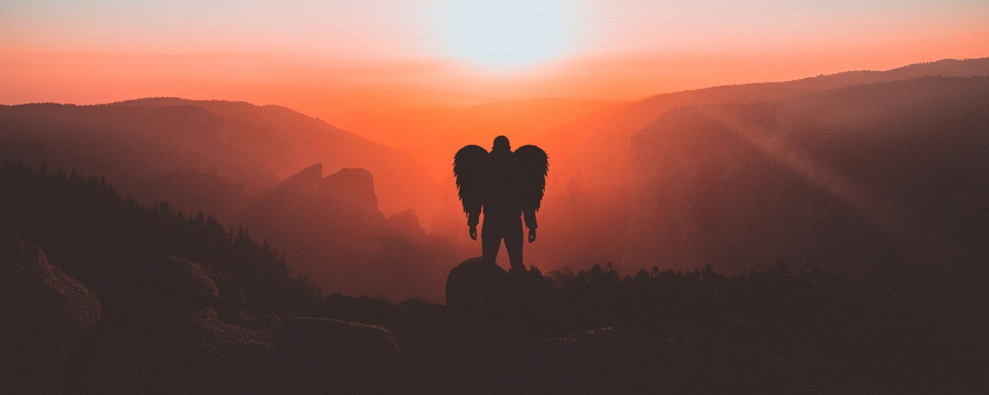 Angel silhouette on top of a cliff, at sunset